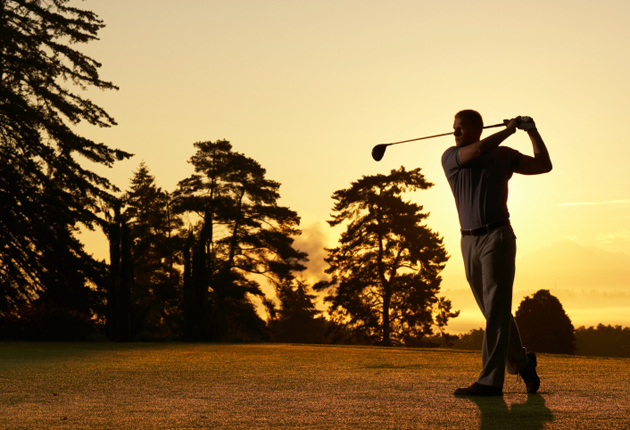 Man golfing at sunset