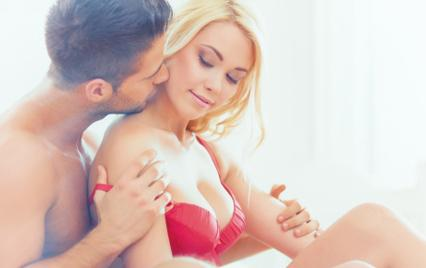 Man kisses woman in red lingerie during foreplay