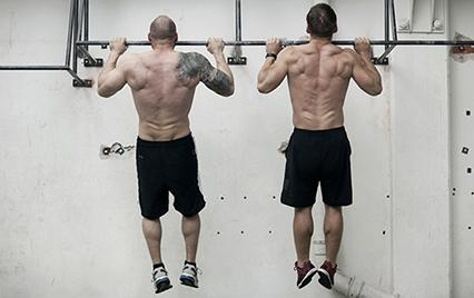 two men working out at a CrossFit box