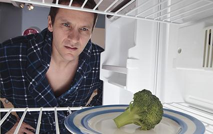 Man looking at broccoli in the fridge