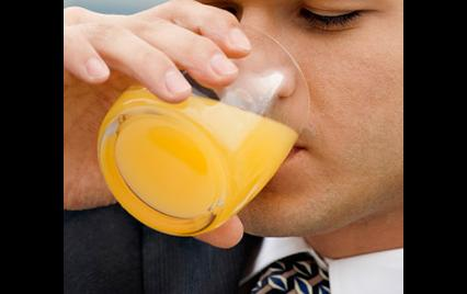 man drinking glass of orange juice