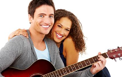 woman sitting with man playing a guitar
