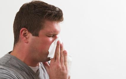 Man with allergies blows nose