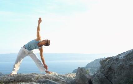 Man performs yoga triangle pose on mountain
