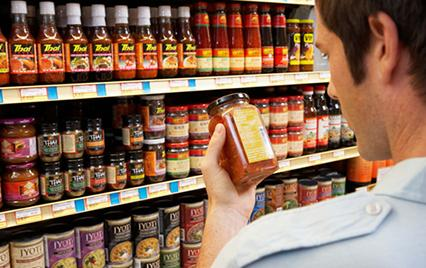 man reading nutriton label in grocery store