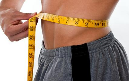 man measuring waist to lose weight