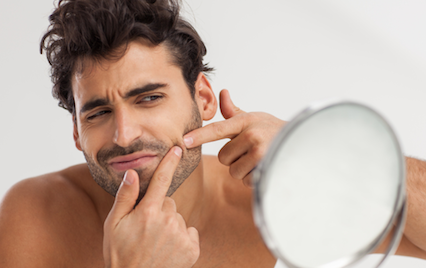 Man looking in mirror popping pimple