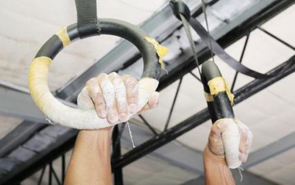 man's hands on gymnastics rings