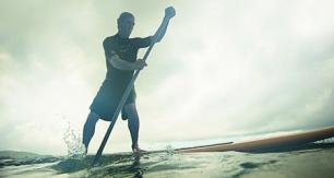 Man rows standings up on paddleboard