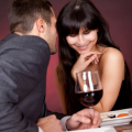 Man whispering in woman's ear over dinner