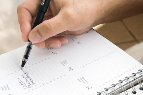 Man writing in calendar