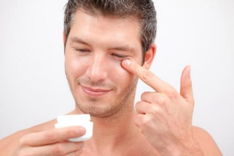 Man putting on eye cream