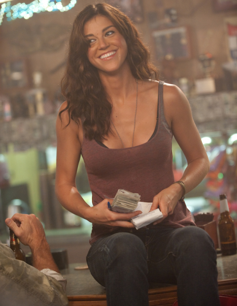 Adrianne Palicki sitting on a bar holding money