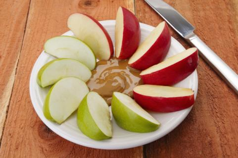 apple slices with peanut butter on a plate with knife