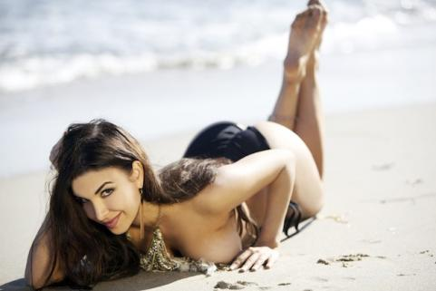 Mayra Veronica laying in the sand