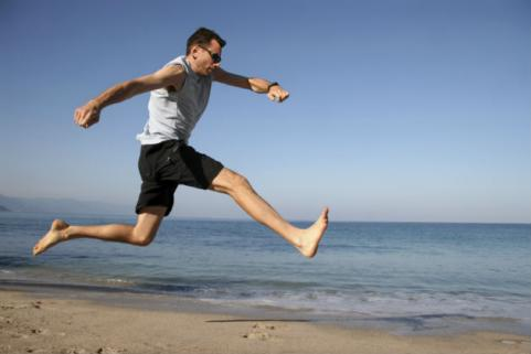 man running barefoot on the beach
