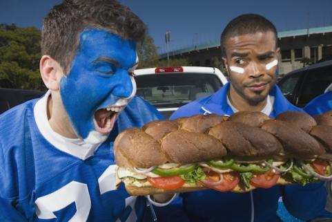 Football fans eating a sub