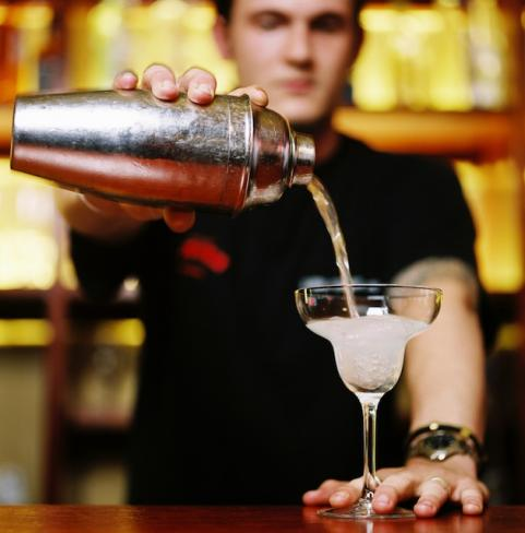 Man with shaker pouring cocktail