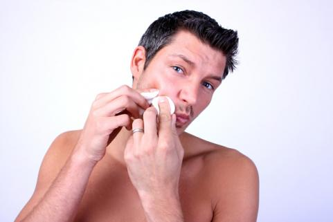 man pinching acne breakout