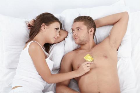 couple in bed holding condom