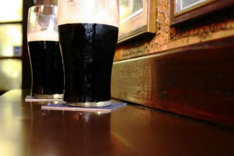 two dark beers sitting on bar