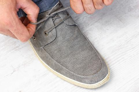 man tying shoelaces on grey shoe