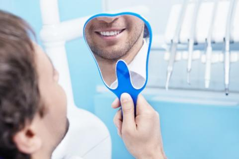 Man looking at his teeth in a mirror