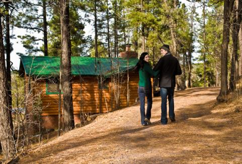 guy and girl walking to log cabin