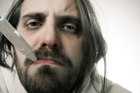 Man with a common cold holding a thermometer