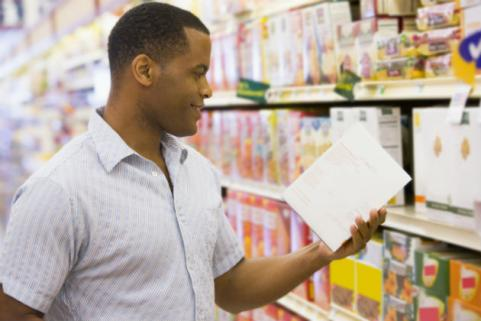 man reading nutrition label at grocery store
