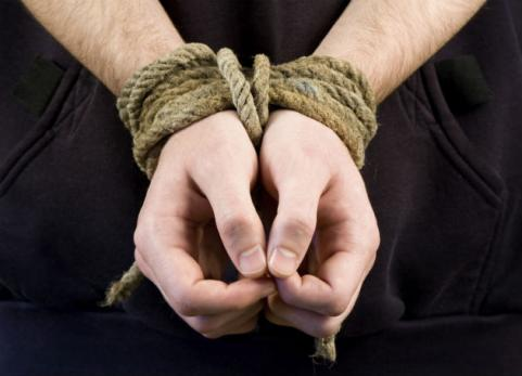 man's wrists tied up