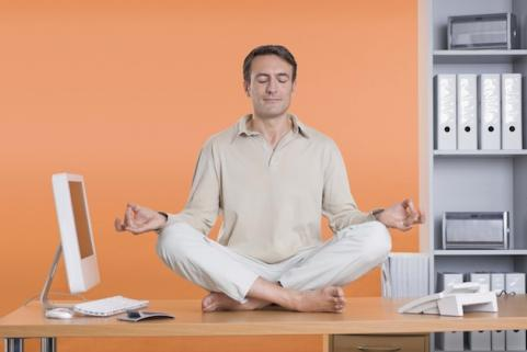 Man meditating on his desk to chill out