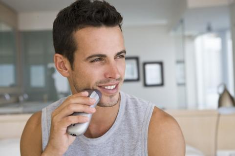 Man shaving with electric razor