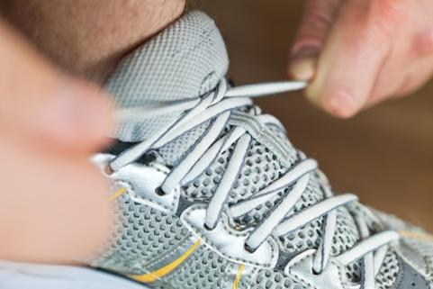 Man tying running shoe