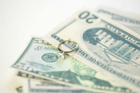 engagement ring on pile of money