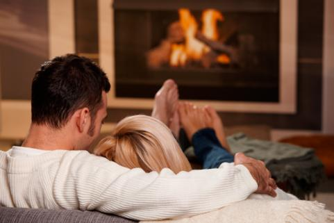 guy and girl sitting in front of fire