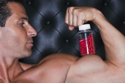 trainer making muscle with supplement bottle