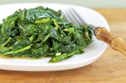 White plate with sauteed spinach and garlic
