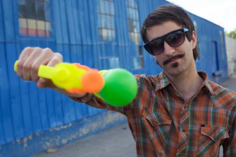 man with a moustache holding a squirt gun