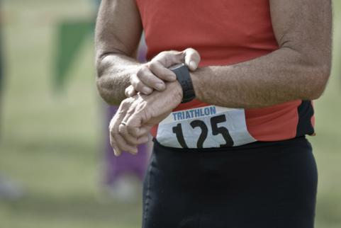 Triathlete checking time on sports watch