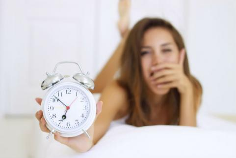 woman with alarm clock in bed