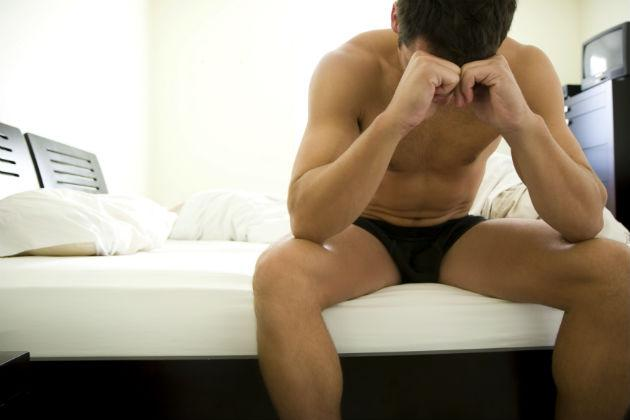 man sitting on bed in underwear