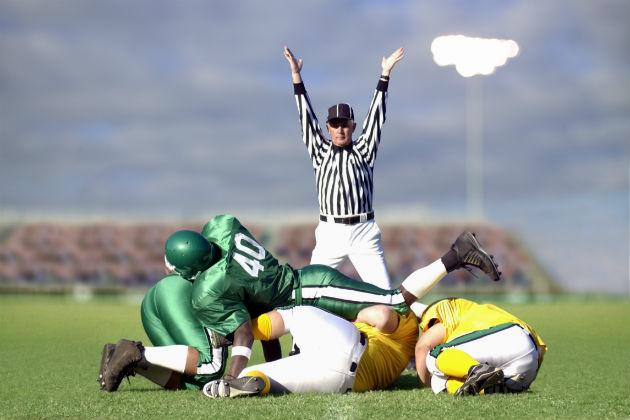 referee giving touchdown sign on football field