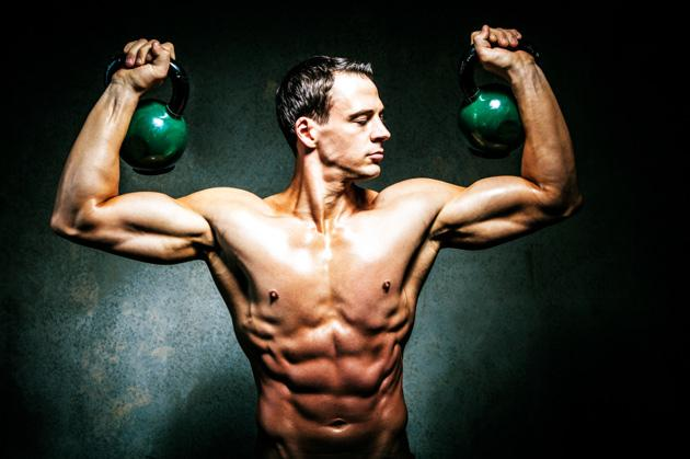 man lifting kettlebells for increased muscle definition