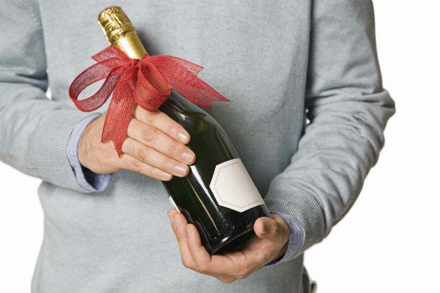 man holding bottle of champagne with a bow