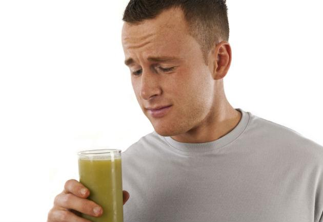 man drinking green juice