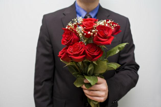 Guy in suit holding flowers