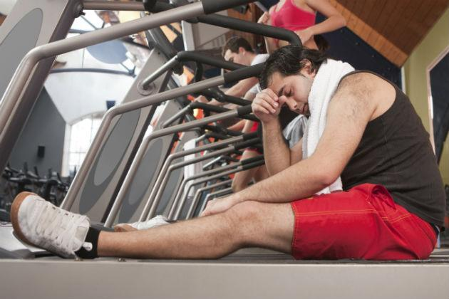 man feeling dizzy sitting on treadmill