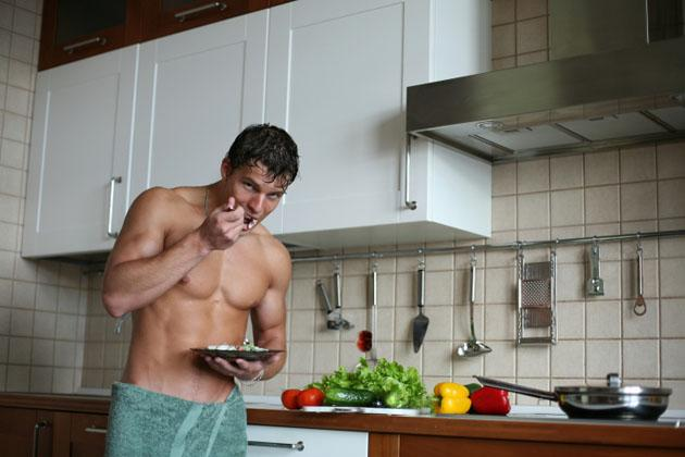 shirtless man eating in the kitchen