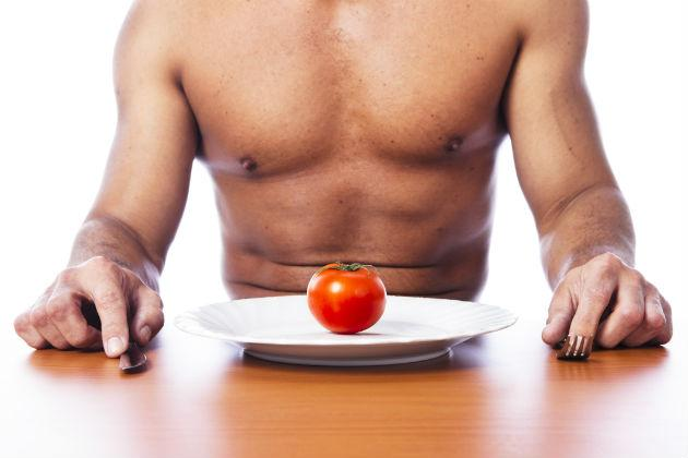 shirtless man eating tomato